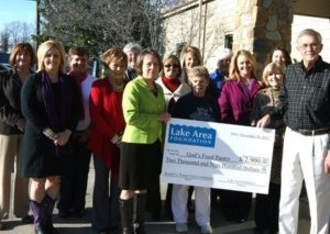 A group stnading outside holding a Lake Area Foundation check made out to God's Food Pantry